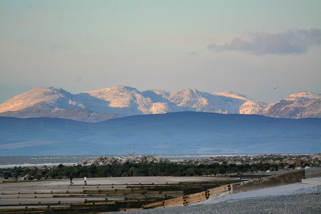 View of a snowy Lake District from Cleveleys beach. Snow at the seaside